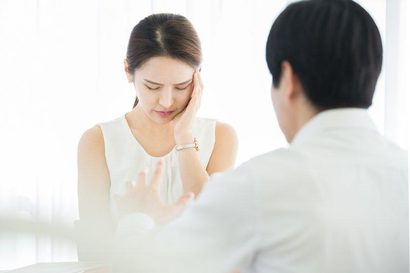 左ひじをついて困っている女性と対面に座って話しをしている男性
