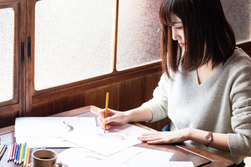 席に座って絵を描いている女性