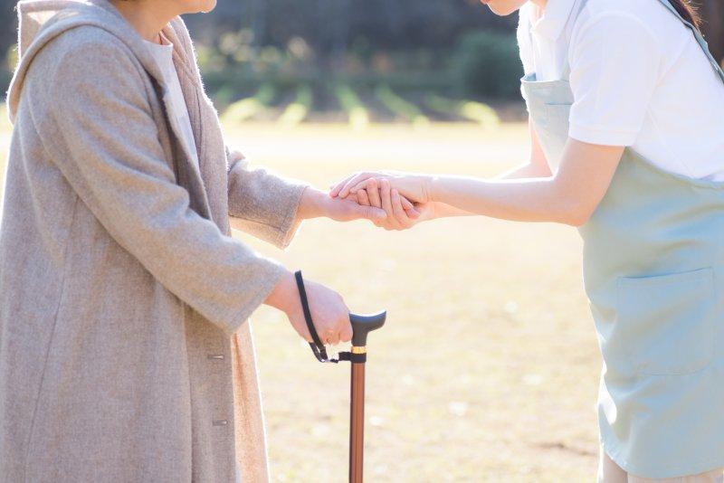 杖を突いて歩く初老女性とサポートするスタッフ