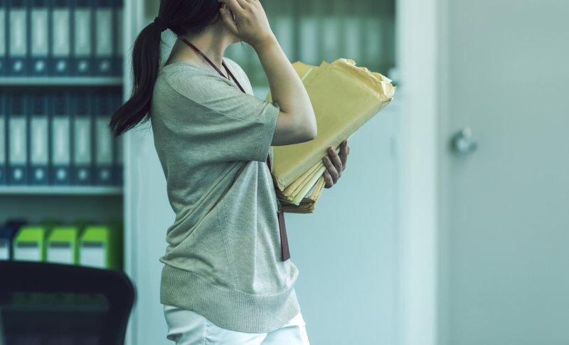 オフィスで何通もの封筒を片手に持ち急いで移動している女性