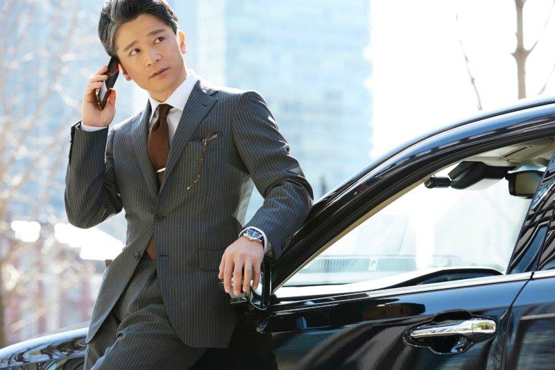 車に寄りかかり電話をするビジネスマン