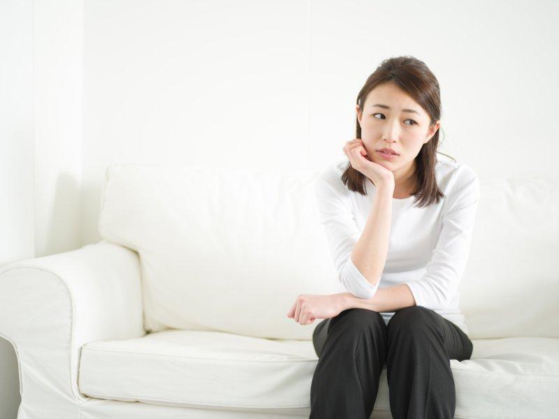 ソファに腰かけて右手で頬杖をついて悩んでいる女性