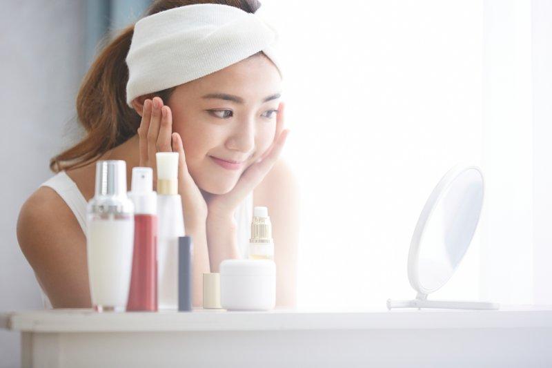 鏡で自分の顔を見ながらスキンケアする女性