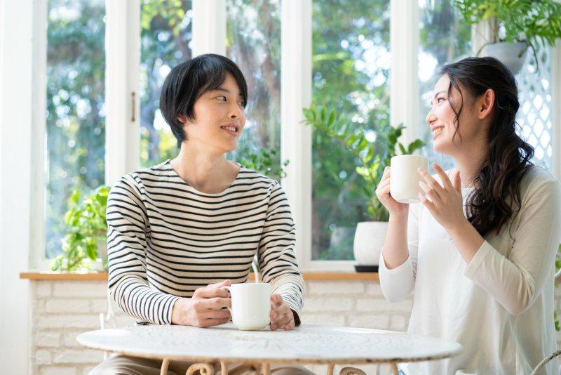 カフェでコーヒーを飲みながら談笑する男女
