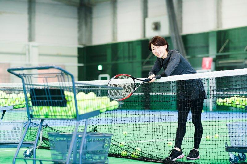 テニスコートでネットに腕を乗せている女性