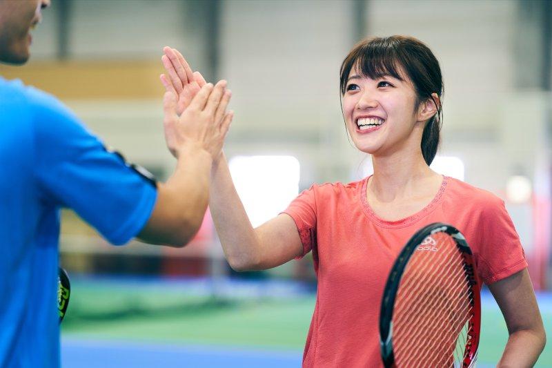 テニスコートでハイタッチをしている男女