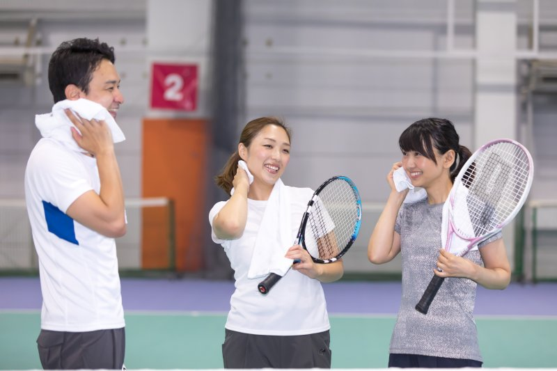 テニスコートで汗を拭く女性2名と男性1名