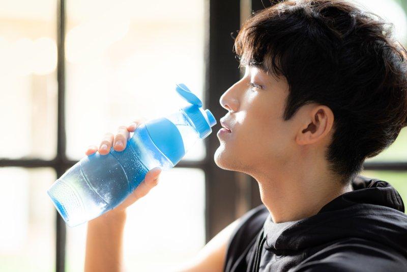 運動中の男性が水を飲んでいる