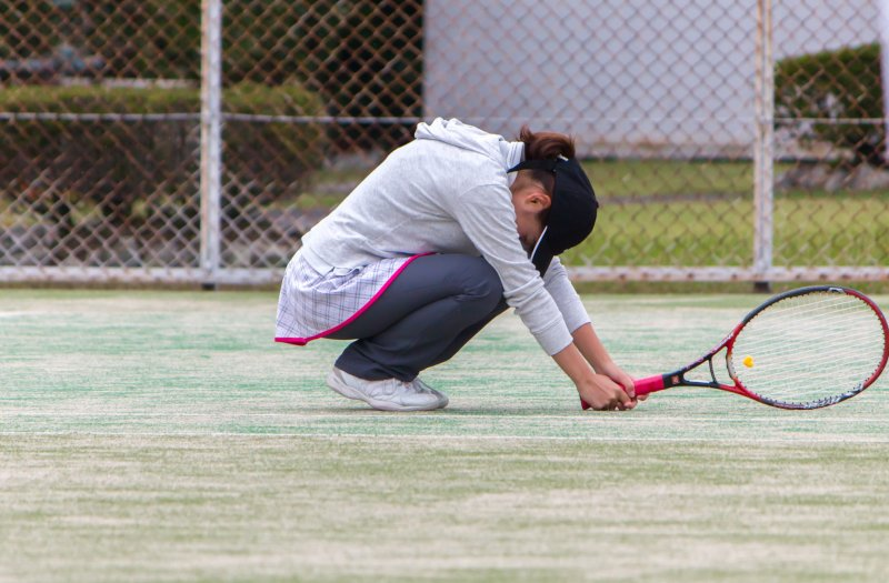 テニスコートでラケットを持ってしゃがみ込む女性