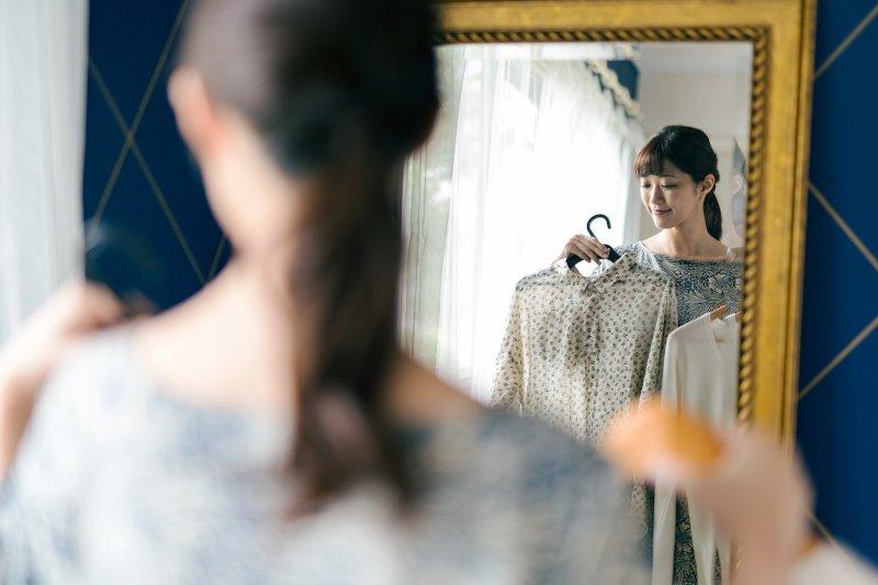 鏡の前で洋服を選んでいる女性