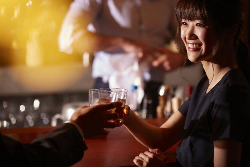 バーで乾杯している男女