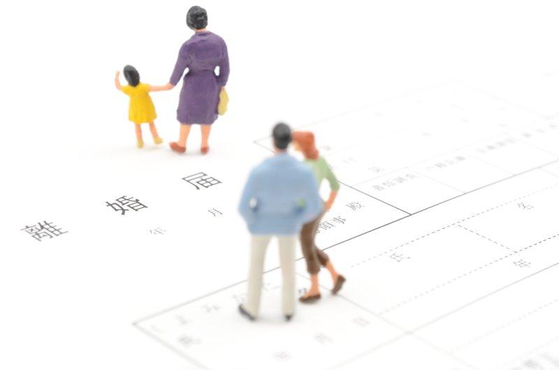 離婚届の上に成人男性1名成人女性2名子供1名の人形が乗っている