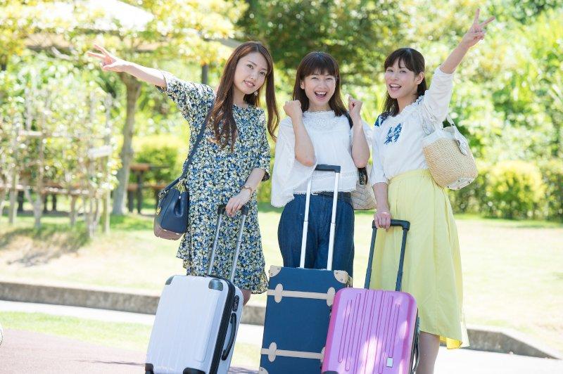 スーツケースを持った女性3人が笑顔で片手を上にあげている