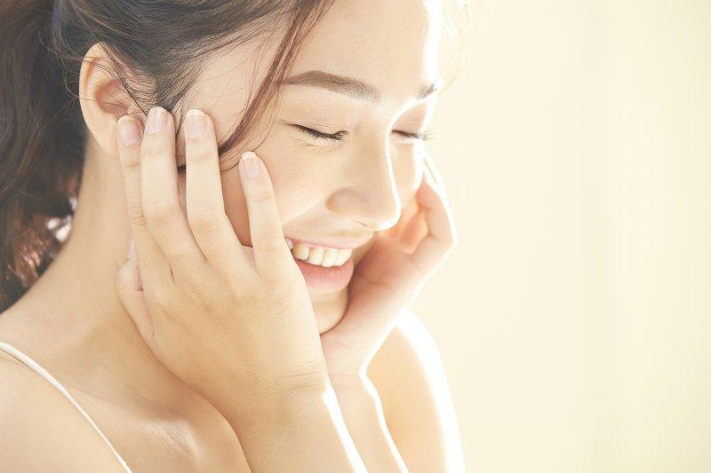 若い女性が両手を顎に当て笑顔で目を閉じている