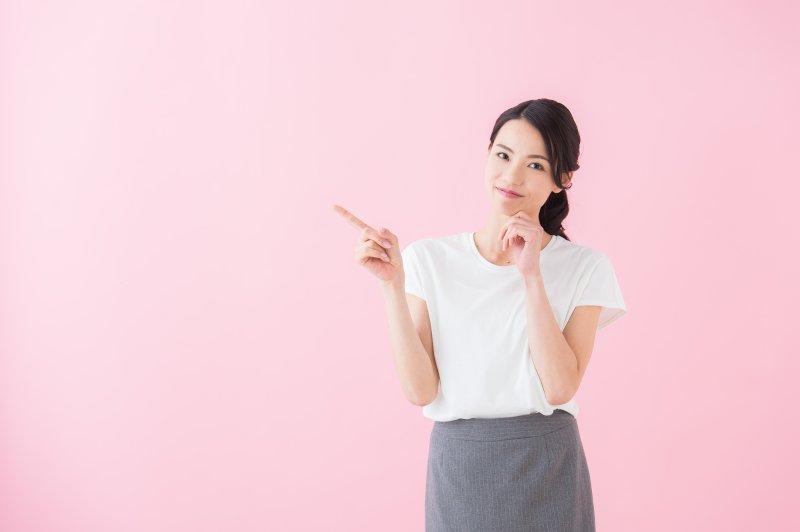 女性が右の人差し指で右上を指さしている