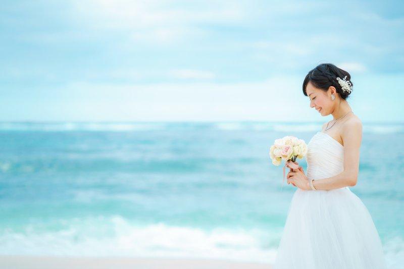 海を背景して立っている新婦