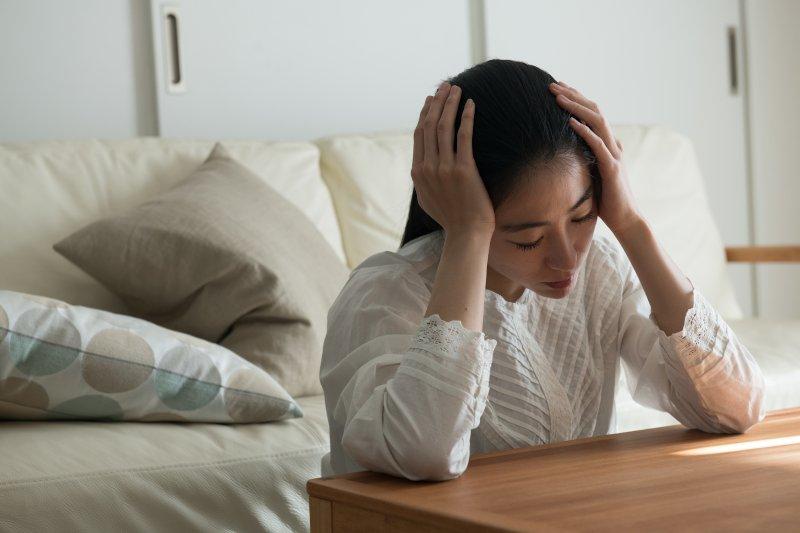 机に両肘をつき両手で頭を抱えている女性