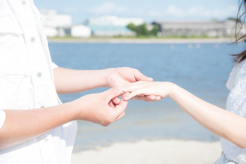 浜辺で向かい合って手を握るカップル