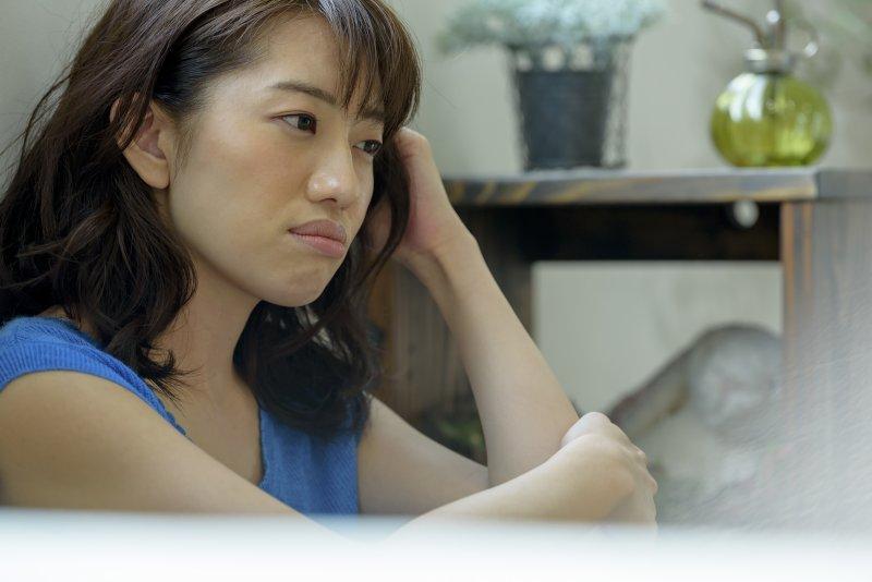 床に座って左手で頭を抱えて悩んでいる女性