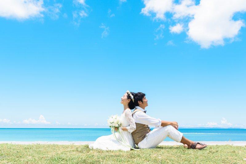 芝生の上で背中合わせに座り海を背景にした新郎新婦