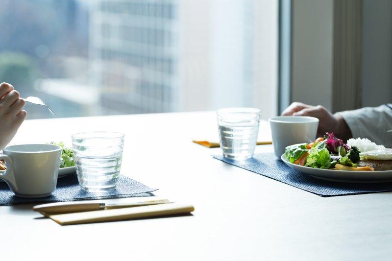 テーブルで向かい合って食事をしている男女