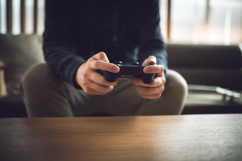 ゲームのコントローラーを握る男性