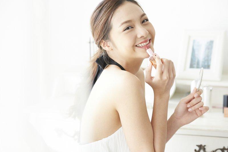 口紅を塗っている女性