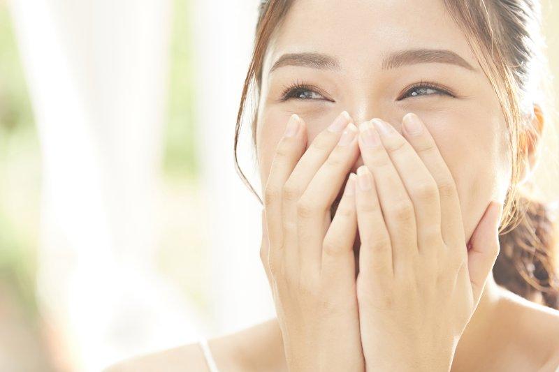 笑顔の口元を両手で覆っている女性