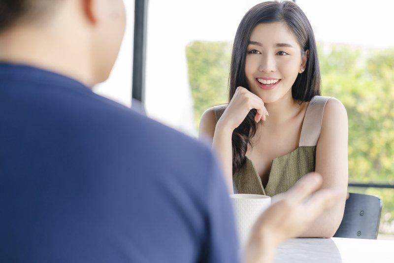 テーブルの対面に座り会話をしている男女