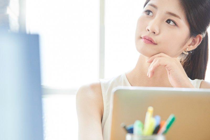 PCの前で左手を顎にあて右斜め上を見ている女性