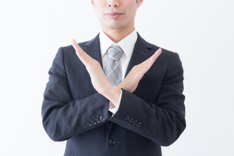男性が胸の前で両手でバツ印を作っている