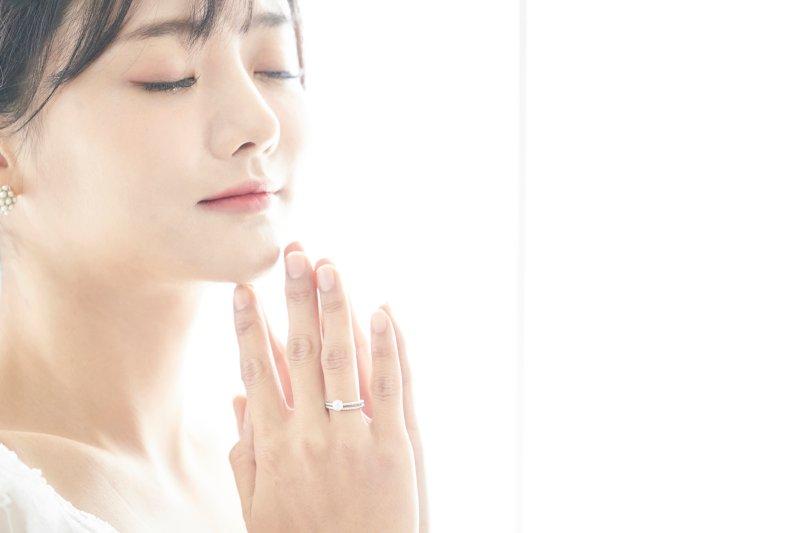 右の薬指に指輪をして両手を合わせて目をつぶっている女性