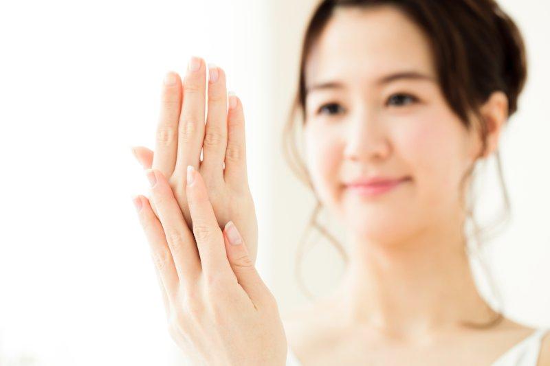 両手をそろえて顔の前にあげている女性