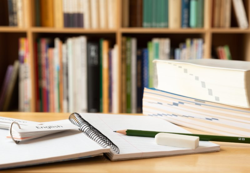 机の上に本や筆記用具が重なっている