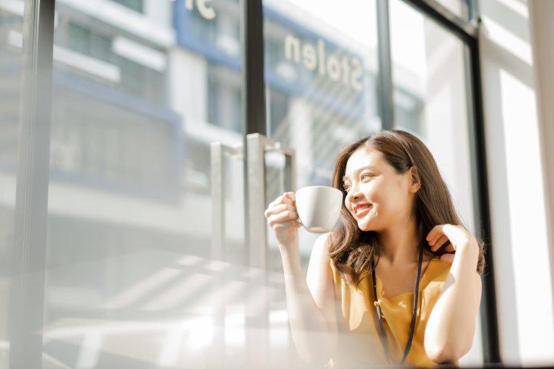 窓際でコーヒーを飲んでいる女性