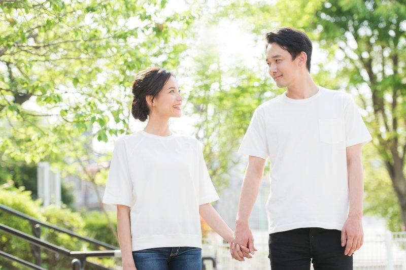 お揃いの白Tを着て手を繋いで外を歩いているカップル