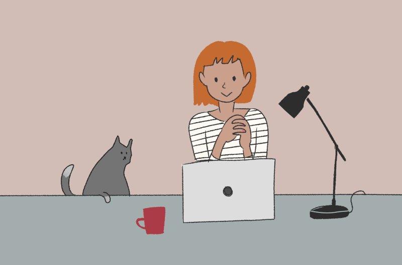PCが置かれた机の前に座ってコーヒーを飲む女性と飼い猫