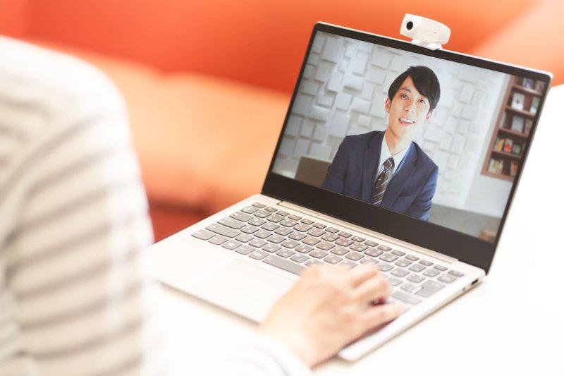 PCに映る男性の画像とPCの前に座っている女性