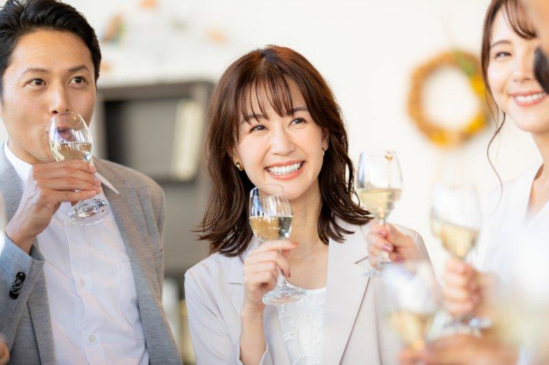 partyで談笑しながらお酒を飲む女性