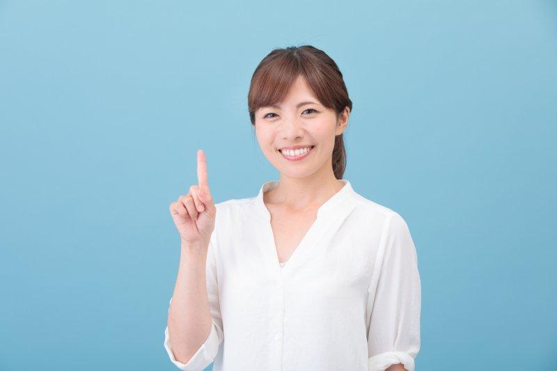 人差し指を立ててポイントを示す女性