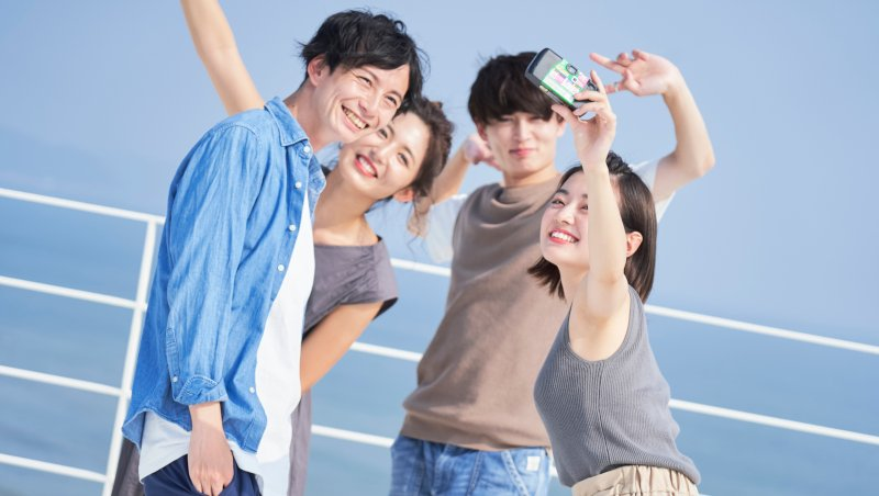 男女友達4人がスマホで写真を撮っている